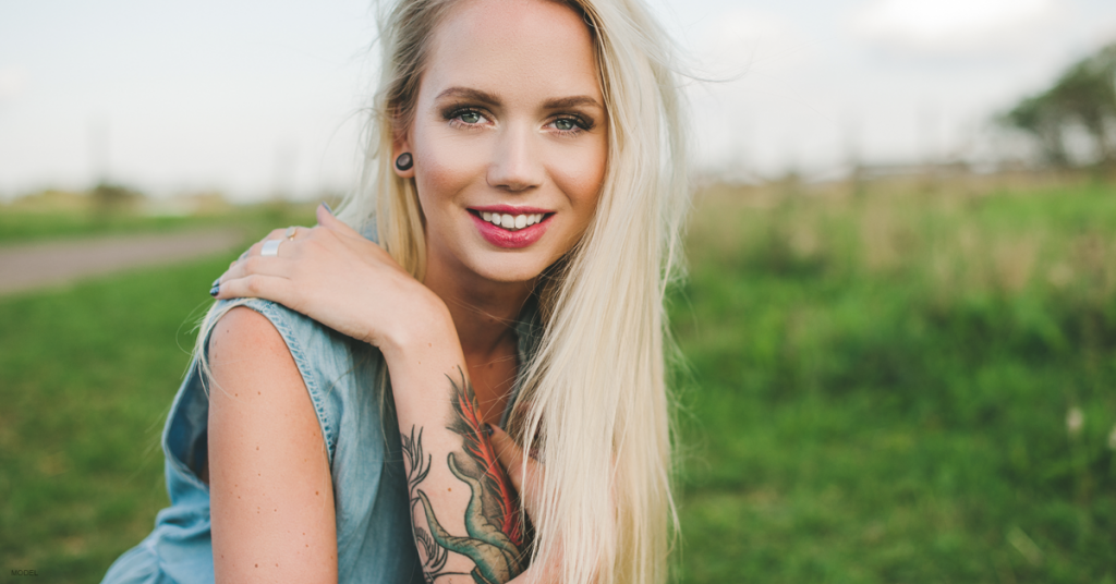 Blonde woman kneels in a grassy field with her hand on her shoulder, showing the colorful tattoo on her forearm.