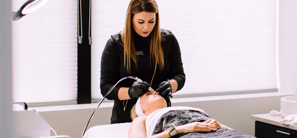 Staff member performing laser skin treatment