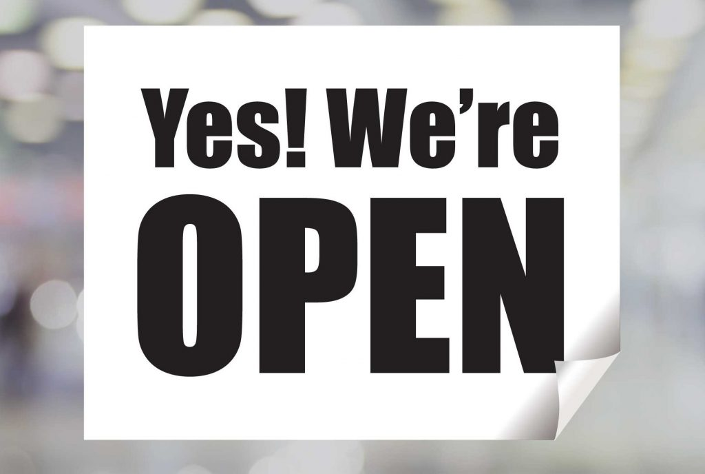 White sign with black lettering that says Yes! We're Open.