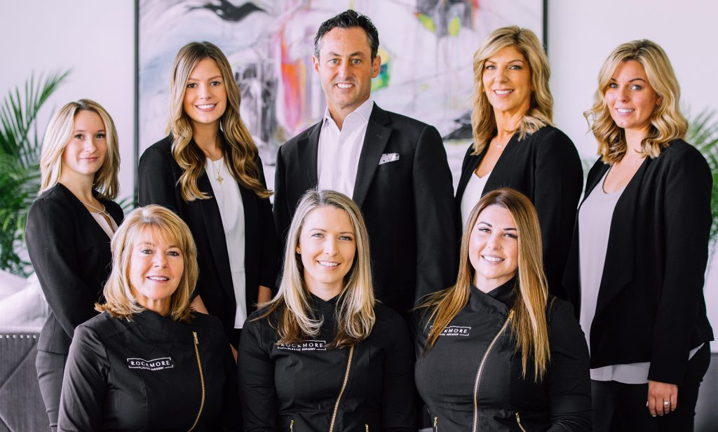The Rockmore Plastic Surgery team, wearing black suits and white shirts or black uniforms, stands in the office lobby.